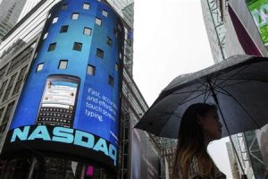 A woman holds an umbrella as she walks past the Nasdaq MarketSite in New York's Times Square
